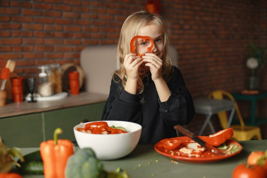 A child holds a red pepper in front of a kitchen table.