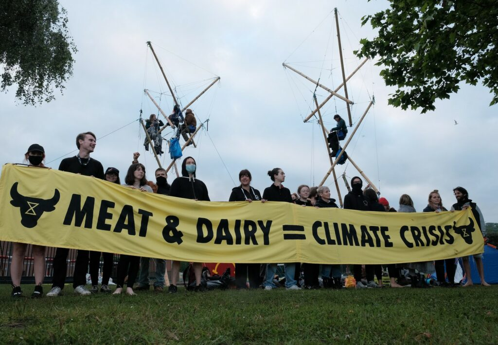 Animal Rebellion holding a banner, saying meat & dairy = climate crisis.